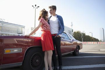 A flirtatious rockabilly couple standing next to a vintage car, Berlin, Germany