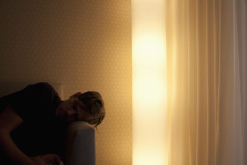 Man lying on couch beside glowing electric light