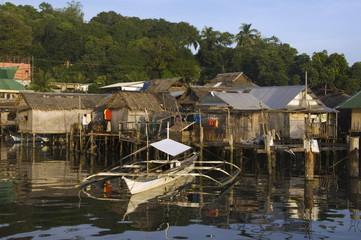 Waterfront stilt houses and catamaran fishing boat, Coron Town, Busuanga Island, Palawan Province, Philippines, Southeast Asia, Asia