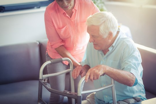 Senior woman helping senior man to walk with walker