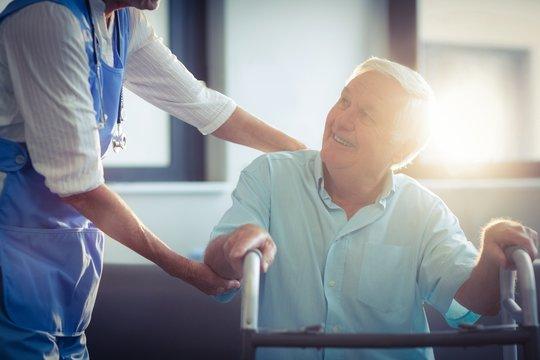 Female doctor helping senior man to walk with walker