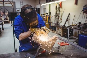 Welder cutting metal with grinder in workshop