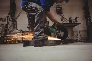 Welder cutting metal with grinder