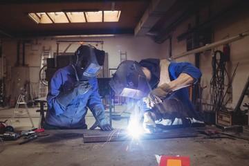 Welder colleague working on a piece of steel