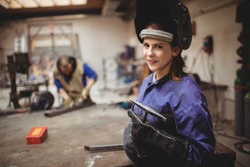 Female welder in protective workwear with colleagues