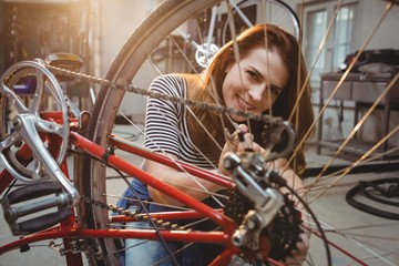 Woman repairing a red bicycle
