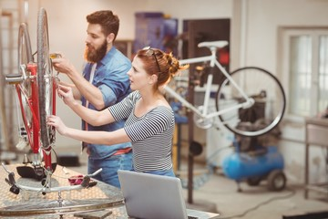 Duo of colleague repairing a bicycle