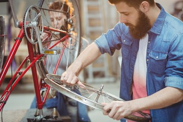 Side portrait of a hipster repairing a bicycle