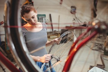 Portrait of woman fixing bicycle behind a bicycle wheel