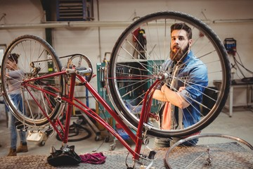 Portrait of hipster crossing arms while standing behind a bicycl