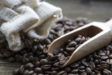 Coffee beans with wooden scoop and linen bag on wooden table
