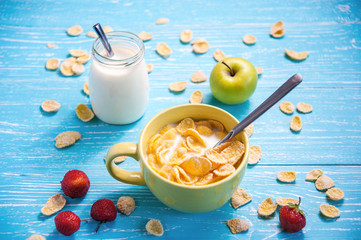 cornflakes with strawberry, apple and jar milk on wooden table