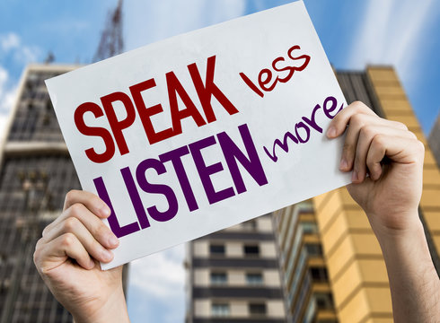 Speak Less Listen More placard with cityscape background