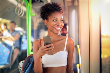 Smiling girl on a bus, chatting with her smart phone