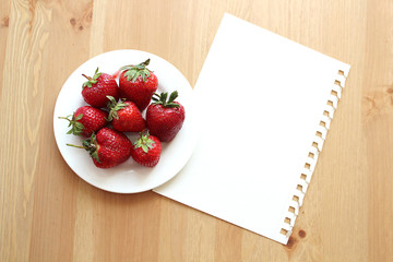 Strawberries in white plate on wooden brown desk.