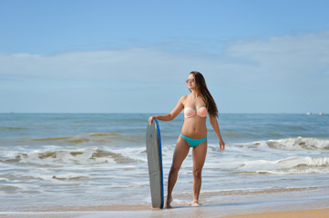 Picture of beautiful girl with bodyboard, ready for fun. Beach background