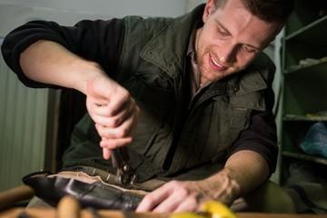 Portrait of a smiling cobbler repairing a shoe