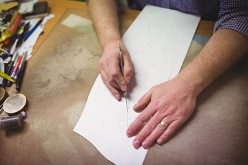 Cobbler cutting a design of shoe from paper