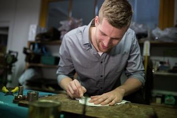 Cobbler cutting a piece of material