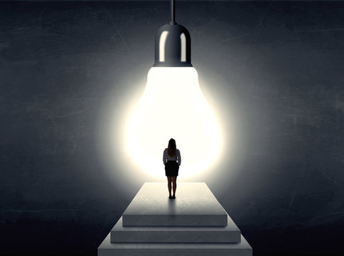 woman standing on a step in front of a huge light bulb