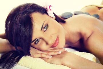 Stone massage, sensual woman getting a hot stone massage at spa salon