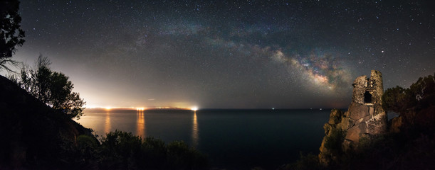 Panoramic view of milky way galaxy over an old fortress