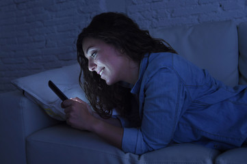 young beautiful woman lying on home couch using mobile phone internet addiction concept