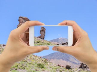 man holds up camera phone at the Teide