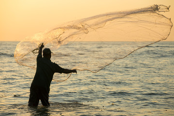 Silhouette of the unidentified Indian fisherman throwing net in sea on sunset in Fort Kochi, India.