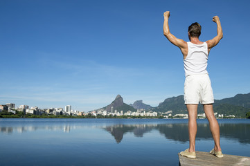 Athlete in white sport uniform standing with champion arms raised in front of Rio de Janeiro Brazil skyline at Lagoa lagoon