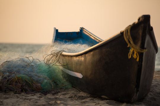 Fisherman boat with fishing nets on the Gokarna beach near the ocean in Karnataka, India