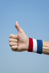 American athlete wearing USA colors red, white, and blue wristband holding thumbs up against blue sky