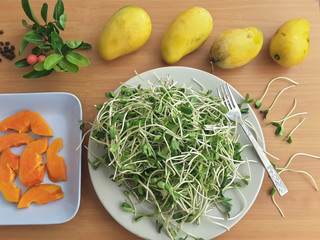 Sunflower sprouts, papaya slices on plate, mango on table