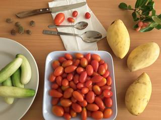 Cucumbers, tomatoes on plate and mango, vegetarian food