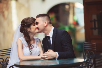 wedding couple sitting at cafe outdoors on sunset