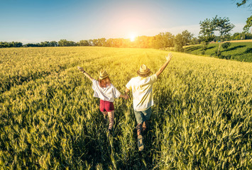 Loving couple running in a wheat field.