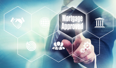 Businessman pushing a mortgage loan concept button.