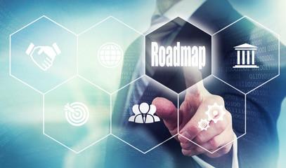Businessman pushing a roadmap concept button.
