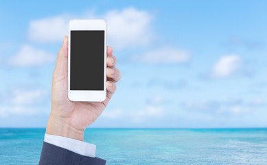 Hand holding mobile phone with blue sea background
