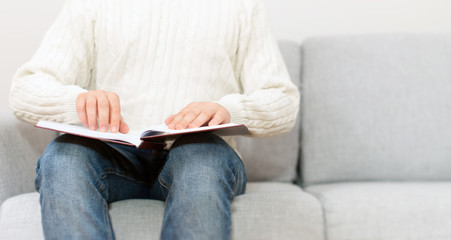 Blind man reading braille book on the couch. Place for your text.