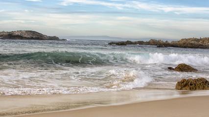 blue ocean waves hitting a sandy beach