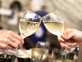 Two People Touching Glasses of White Wine Celebrating an Event