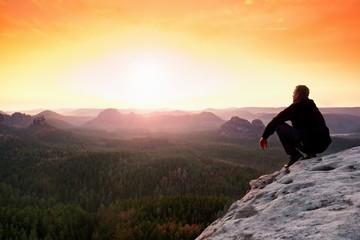 Man enjoing watching orange daybreak in mountains