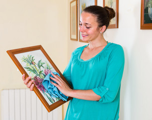 girl cleans picture in her house