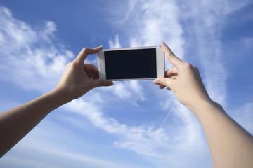 woman use smart phone take a photo of blue sky and beautiful cloud