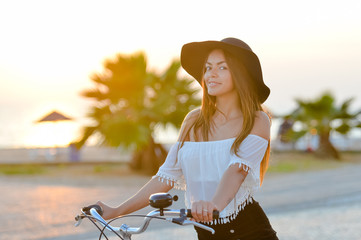 Summer sunset lifestyle image of hipster beautiful woman riding bicycle, having fun, enjoying tropical vacation