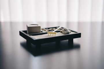 Zen garden with sand, rake, stones, and candle
