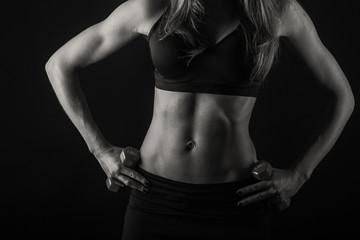 Elegant women trained body on black. Women's fitness