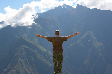 Person standing in front of mountain landscape