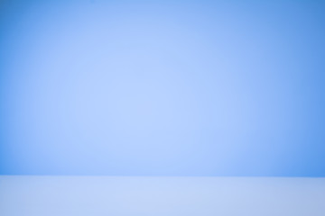 Blue gradient background with a white, reflective desk surface.